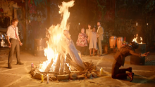 Constantine and Papa Midnite burn the corpses of the spirits