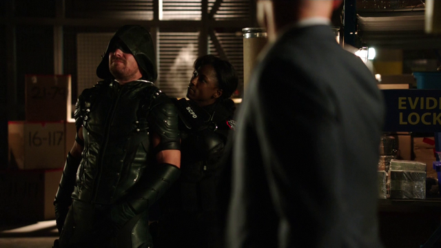 File:Lance watches as Liza Warner holds the Green Arrow hostage.png