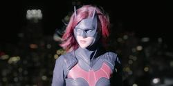 Batwoman olhando para um helicóptero