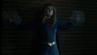 Supergirl stuck to a wall by an Aurafacian's webs