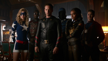 The Justice Society of America watch the imprisoned Legends on security footage