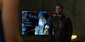 Oliver Queen standing next to a TV showing Sub-Zero..png