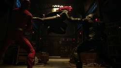 Batwoman subduing the Flash and Green Arrow