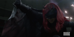 Batwoman covers herself from Crow bullets
