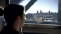 Barry Allen on a train ride, viewing S.T.A.R. Labs from afar.png