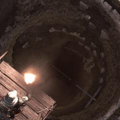 Ezio éclairant la fosse de sa torche