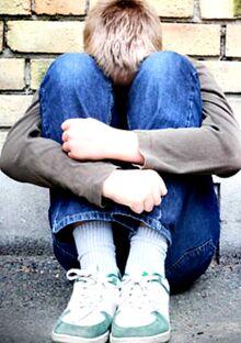 Anxious Autistic teen boy in fetal position