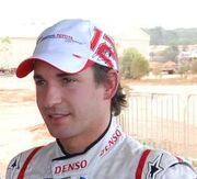 Head and shoulders of a man in his twenties with dark brown hair and eyes. He is wearing a red-and-white baseball cap which displays the Panasonic Toyota Racing logo at the front, and the number 12, with his signature superimposed upon it, on the left side. He is also wearing white racing overalls with red stripes, upon the collar of which the Denso logo is embroidered.