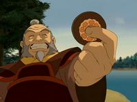 Iroh sostiene la ficha del loto blanco