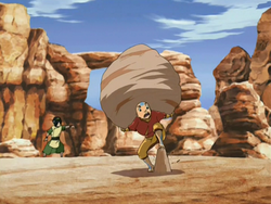 Aang carries a rock