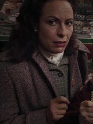 Debora Weston as Woman in Shop