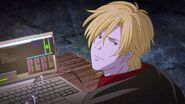 Ash smiles and his laptop besides him