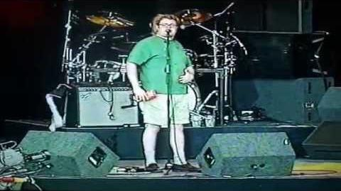 "BNL performing ""$1000000"" at a concert in Britain, in which Steve is presented with a box of ""Cheesey Pasta"""