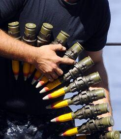 US Navy 090529-N-5345W-126 Gunner's Mate 2nd Class Michael Miller downloads an ammo belt from an MK 38 25mm gun