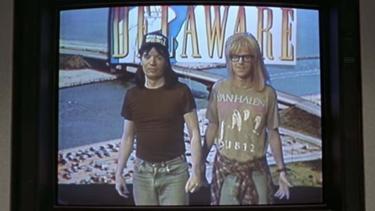 Wayne and Garth stand in front of a green screen showing Delaware.