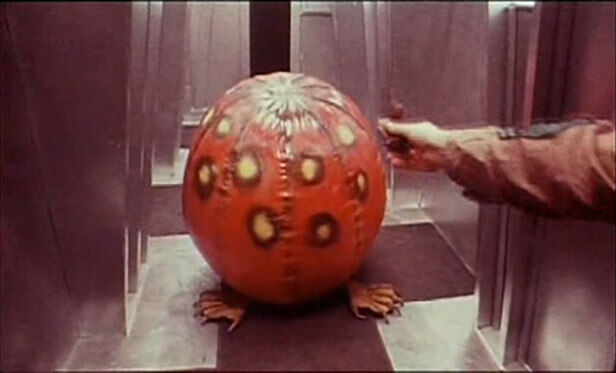 dark-star inflatable red-spotted alien in an elevator being tickled