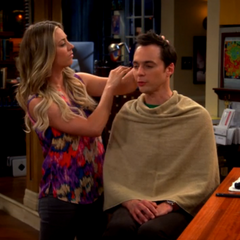 Sheldon getting a haircut from Penny.