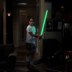Leonard heard a sound and is defending himself with the FX model of Luke Skywalker's light saber.