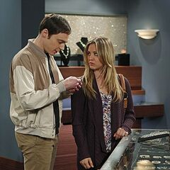 Sheldon and Penny look over an item at a jewelry store.
