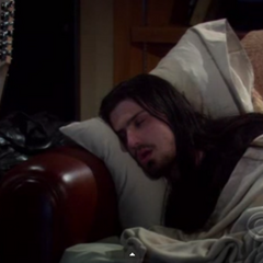 Penny's musician friend asleep on Sheldon's couch.