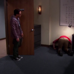 Leonard watches on as Sheldon is stuck with his head in the wall.
