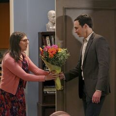 Sheldon giving flowers to Amy.