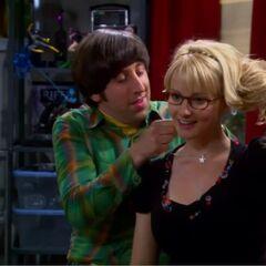 Howard puts the necklace around Bernadette's neck.