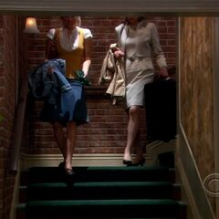 Penny and Beverly walking down the stairs.