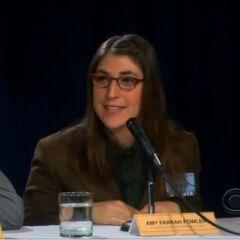 Amy sits next to Raj both as a members of the panel at a science symposium.