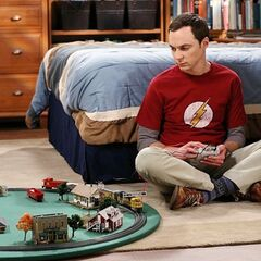Sheldon playing with his train set.