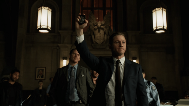 Detective Jim Gordon is seen center-screen, flanked by his colleagues inside a dark, gothic interior. He is walking forward authorotatively, with his hand up in the air, displaying his badge.