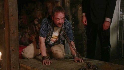 Crowley is seen on his knees with a chain around his neck that is attached securely to the floor.