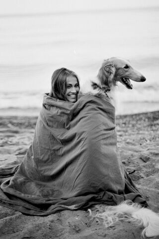 File:A girl and long haired dog wrapped up in a blanket on the beach.jpg