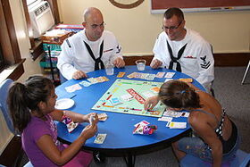 Flickr - Official U.S. Navy Imagery - Sailors play board games with children at the Cameron Community Ministries during Rochester Navy Week