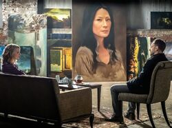 Natalie Dormer guest stars as Jamie Moriarty Irene Adler with Jonny Lee Miller as Sherlock Holmes with a painting of Joan Watson in CBS Elementary Season 2 Episode 12 The Diabolical Kind