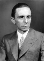 A black and white photo of a man wearing a suit and tie. His body is facing to the left while his head is turned towards the right.