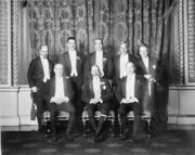 A group pose of eight men in smart evening wear. The King sits in the middle surrounded by his prime ministers.
