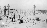 A snowy hill with stone barriers and barbed wire in front, and a distant bunker in behind.
