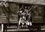 Men waving from the door and window of a rail goods van