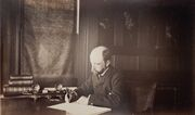 Henry Adams seated at desk in dark coat, writing, photograph by Marian Hooper Adams, 1883