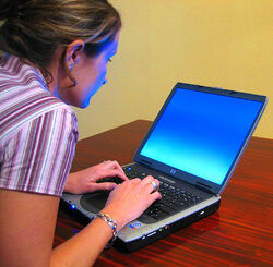 1024px-Woman-typing-on-laptop2