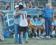 El técnico Pablo Quiroga saludando al goleador Sergio Villordo