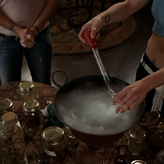 Phoebe filling a vial with the potion.