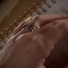 Dumain puts Grams's ring around Piper's finger.