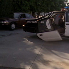 Darryl throws the criminal through the other side of the police car.