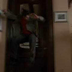 Chris is flung against the door of Piper's bedroom.