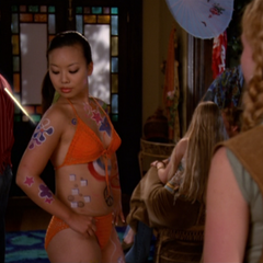 A Witch using Telekinesis on a paint brush to paint flowers on her body.
