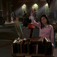 Sara telekinetically moves a book back into the bookcase at Magic School.