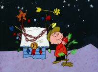 Charlie Brown puts the ornament on the tree