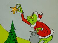 Grinch taking the star off the tree